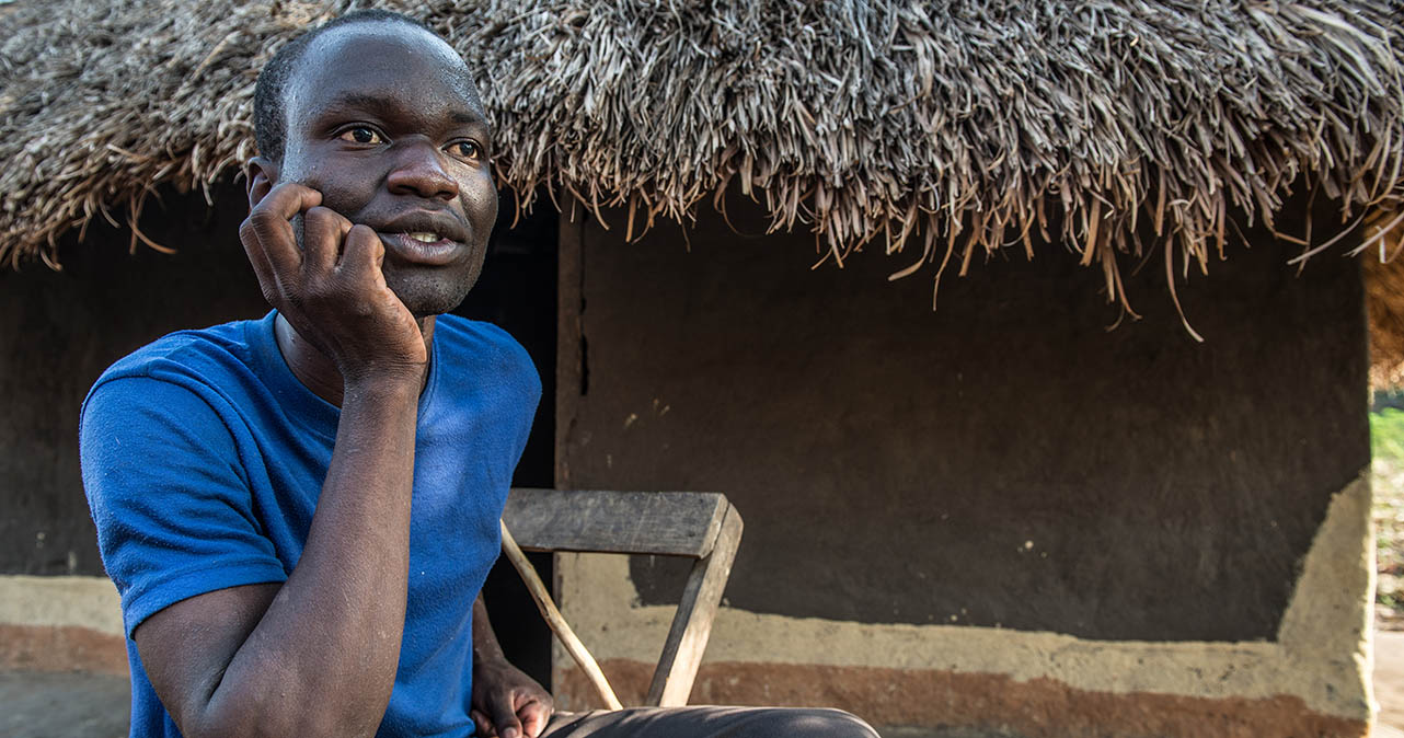 Albert sat on a chair outside a hut, his head resting in his right hand.
