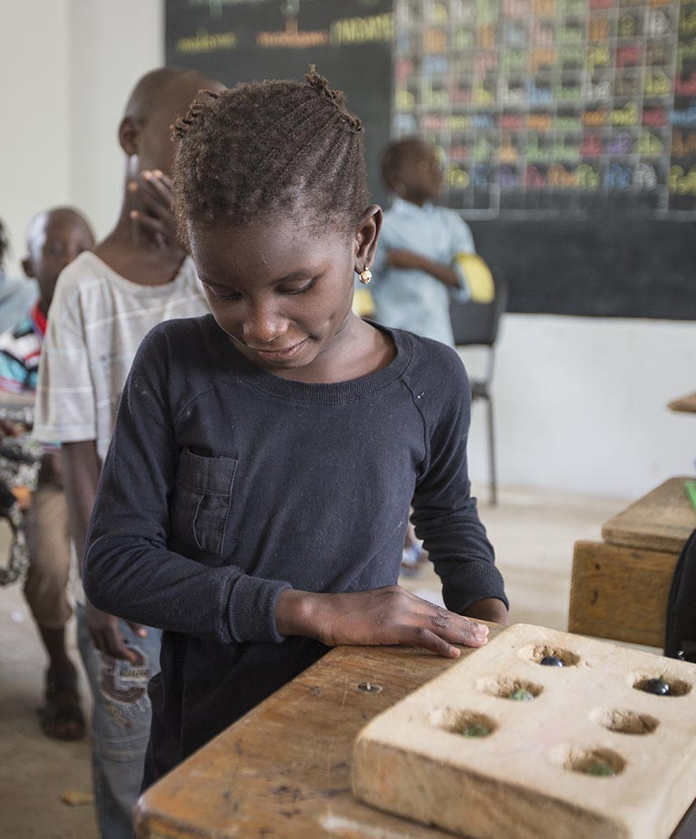 Aminata at her desk next to an assistive tool to help her do maths.