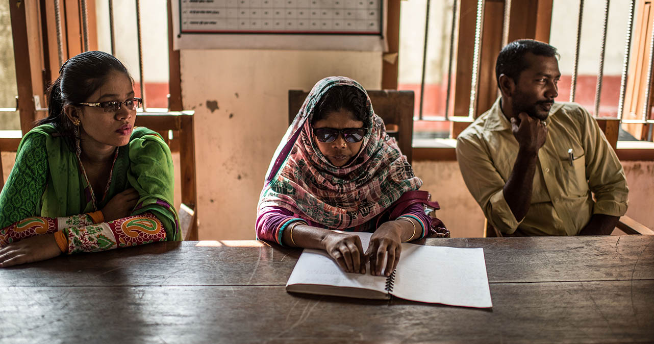 Jahanara sat at a table with a man and a woman. She is reading from a braille book.