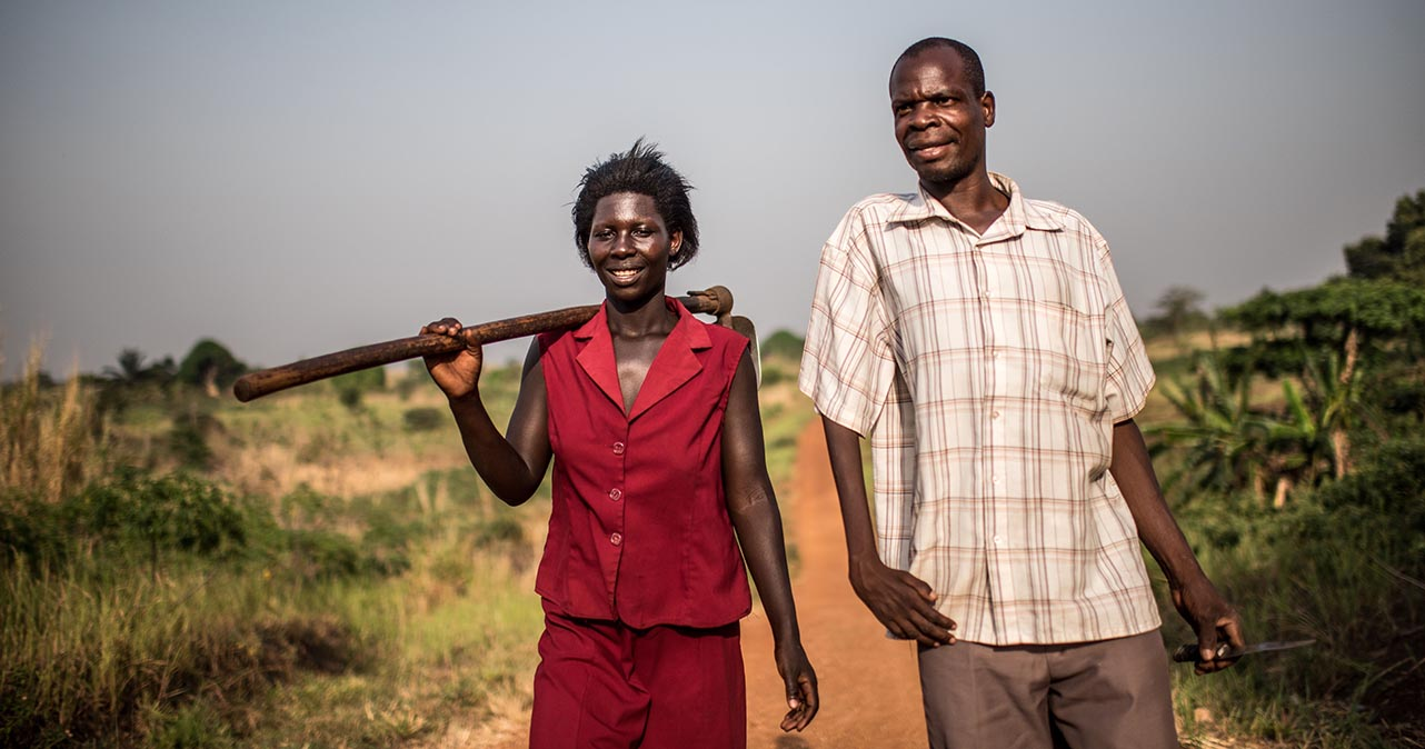 Nicholas and his wife Rose walking on a road. Rose is holding a farming tool over her right shoulder.