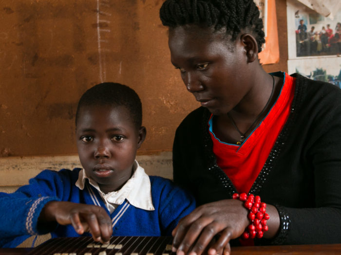 A young woman assists a child using braille in a classroom.