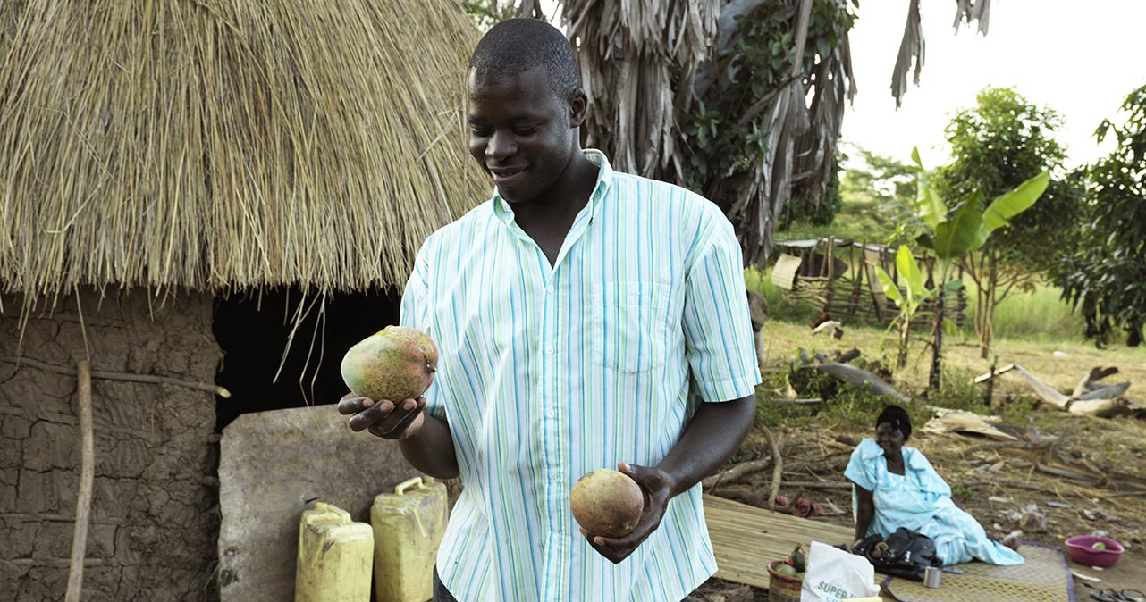 Atugonza holding two mangoes.