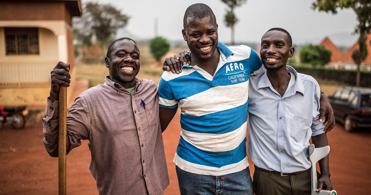 Atugonza and two volunteers with arms around each other.