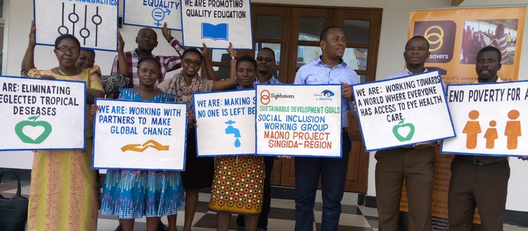 A group of people holding up signs explaining how their work supports the sustainable development goals.