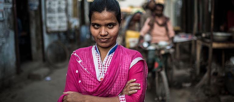 A visually impaired, Bangladeshi woman in a pink dress standing in an alleyway.