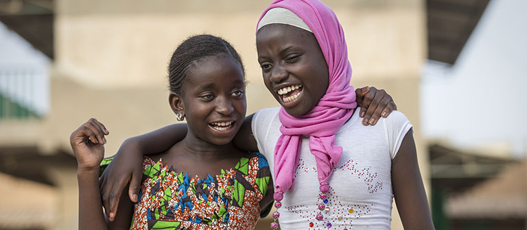 Two young visually impaired girls with arms around each other.