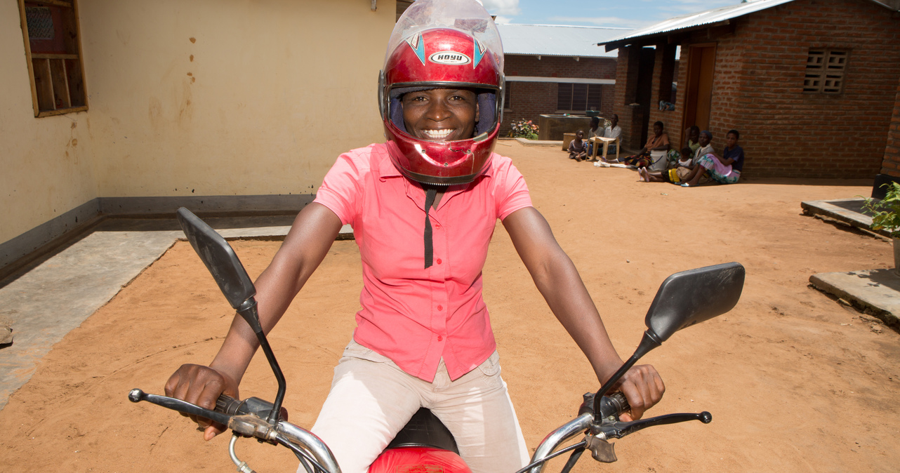 Mirriam sitting on her motorcycle wearing a helmet.