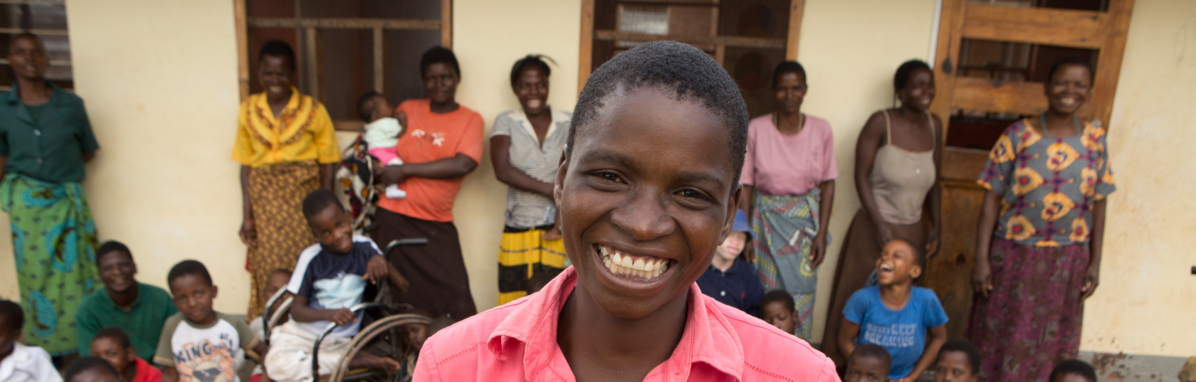 Mirriam smiling in front of a group of children.