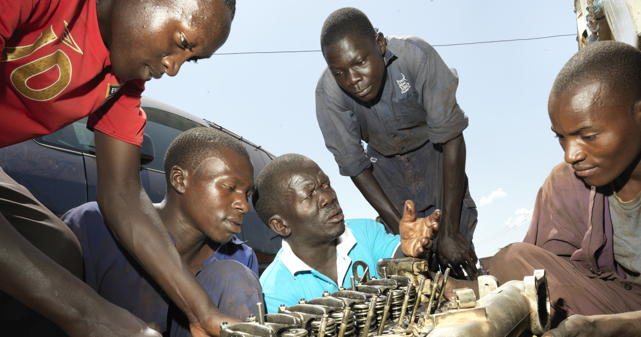 Godfrey working on a van with four students.