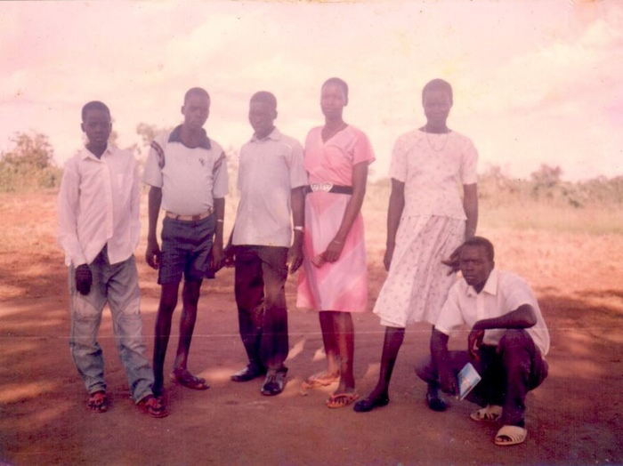 An old photo showing a group of young people standing together.