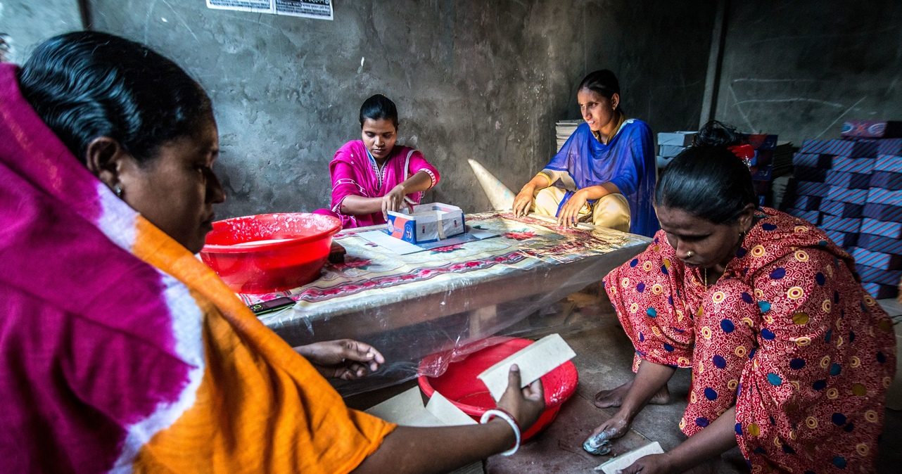 Four women making boxes at a table.