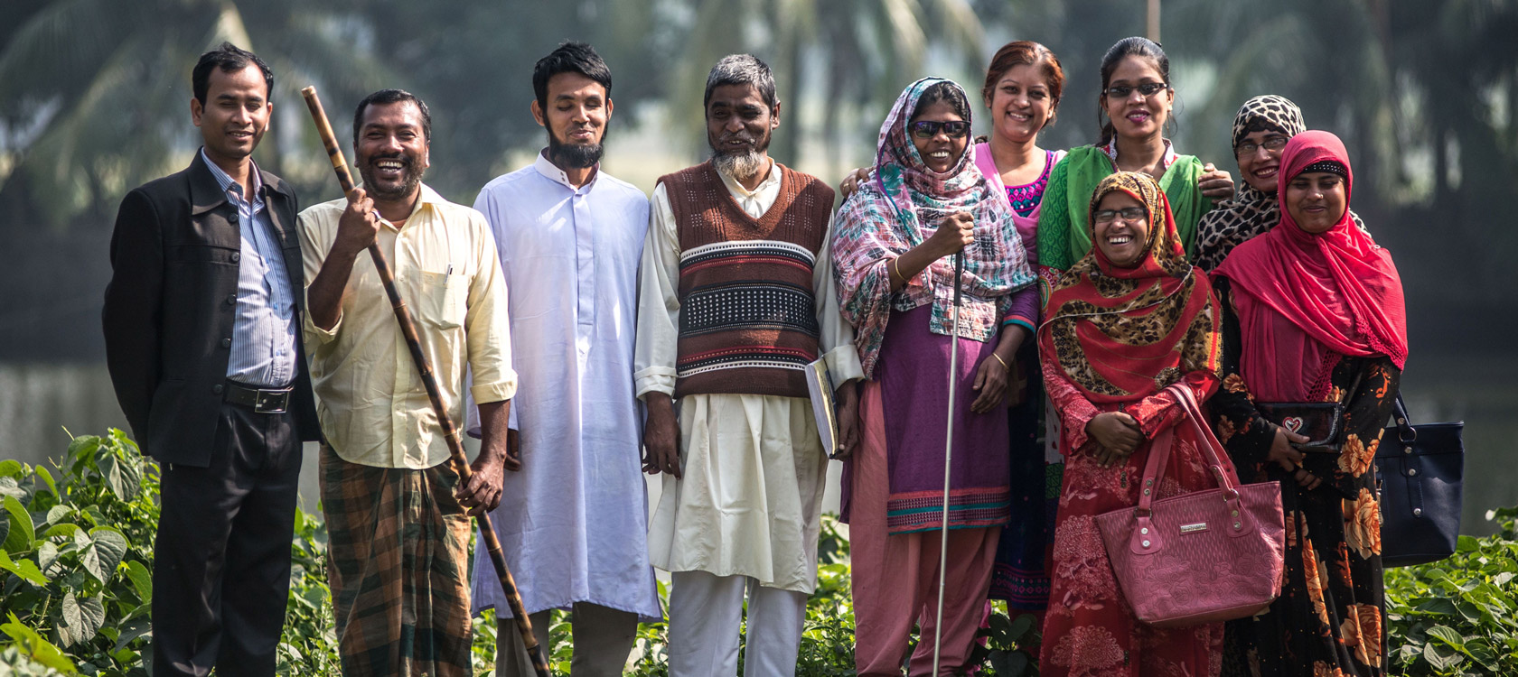Members of a disabled persons organisation from Bangladesh standing in a row outside.