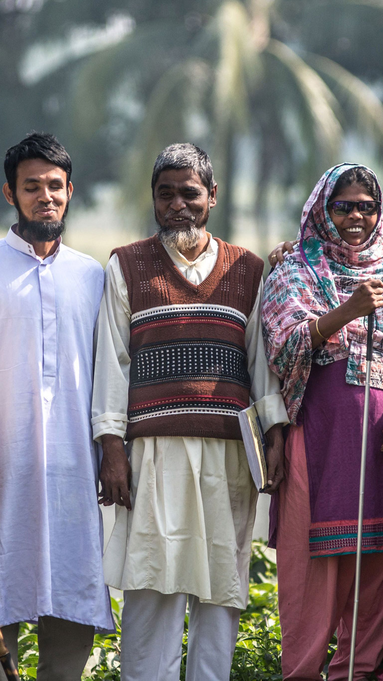 Three members from a disabled persons organisation in Bangladesh standing outside.