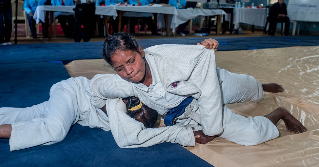 Nikki pinning down another judo competitor on the mat.