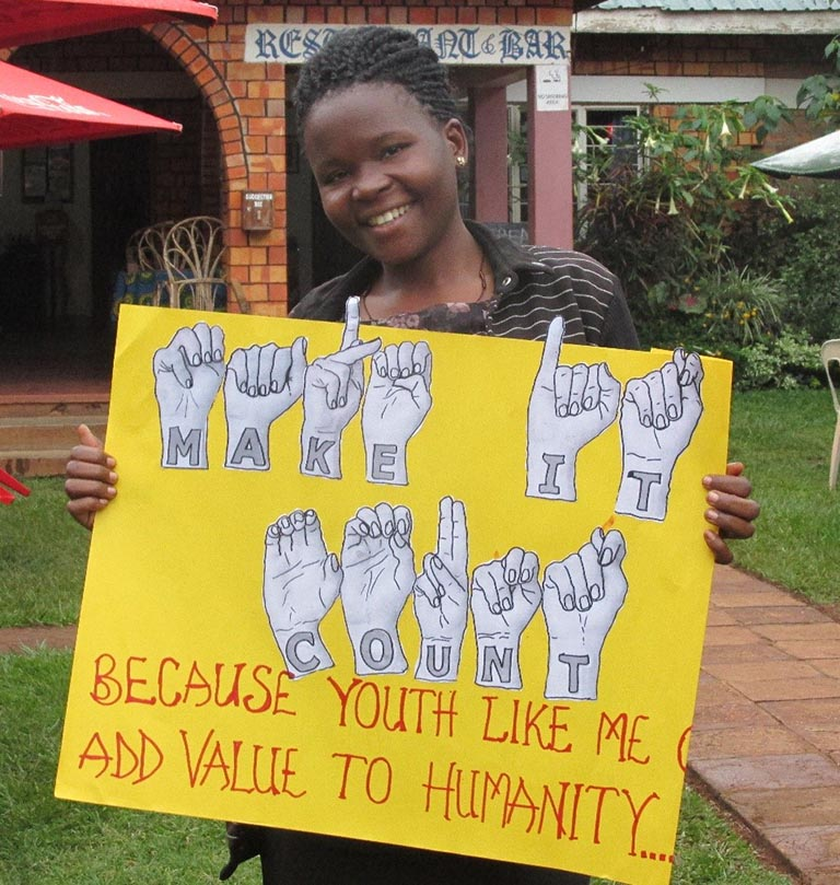 A woman holding a yellow sign which says: Make it count because youth like me add value to humanity.