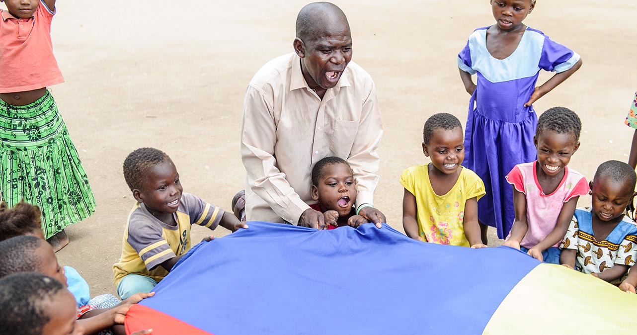 A group of children, including Tapiwa, and their teacher playing with a colourful sheet.