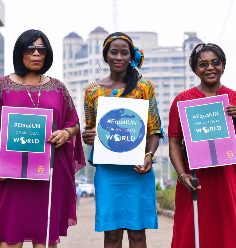 Three women standing outside in a city, with tall buildings behind them. Each woman holds up a sign reading '#EqualUN for an equal world'.