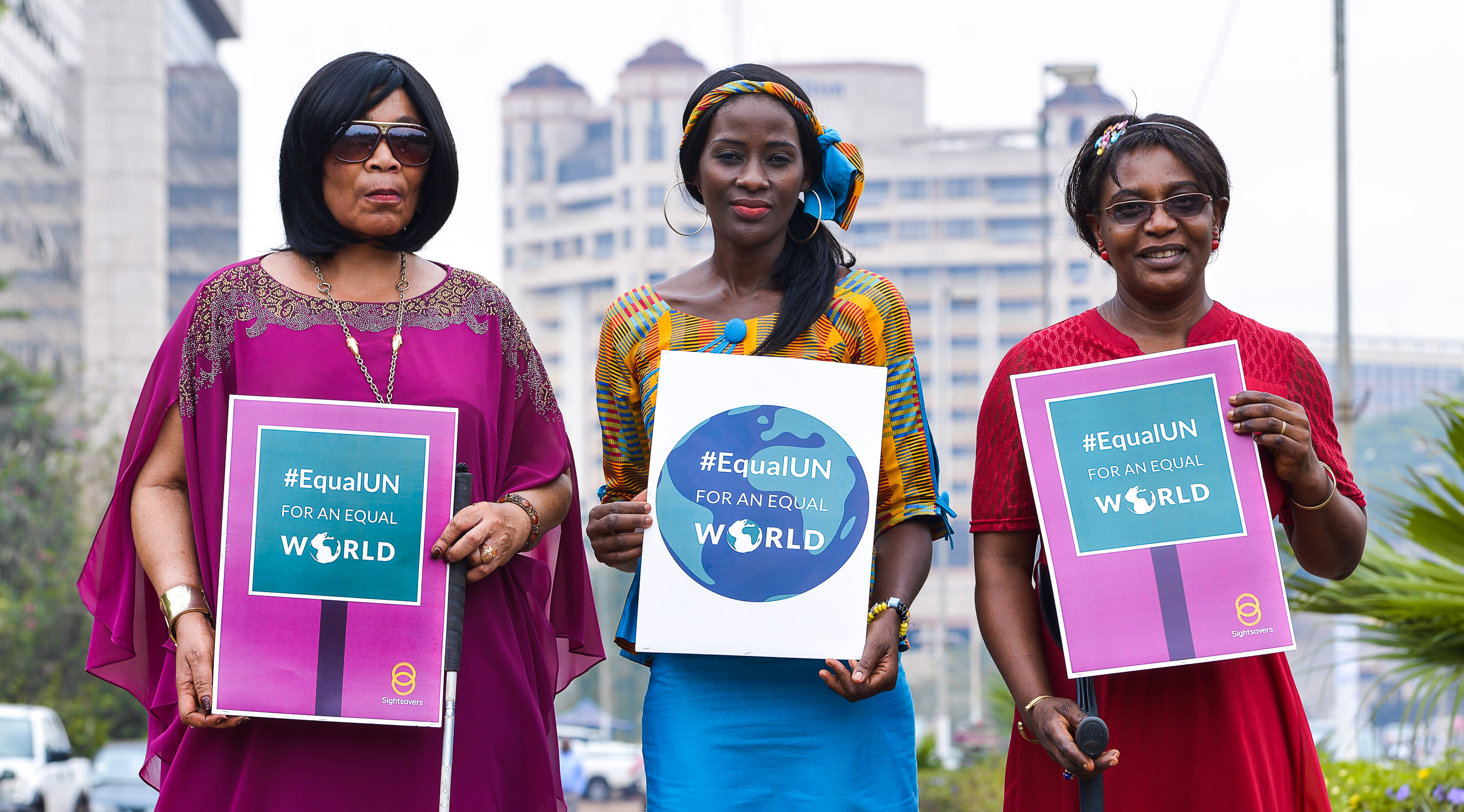 Thre women standing outside in a city with tall buildings behind them. Each woman holds a sign reading '#EqualUN for an equal world'.