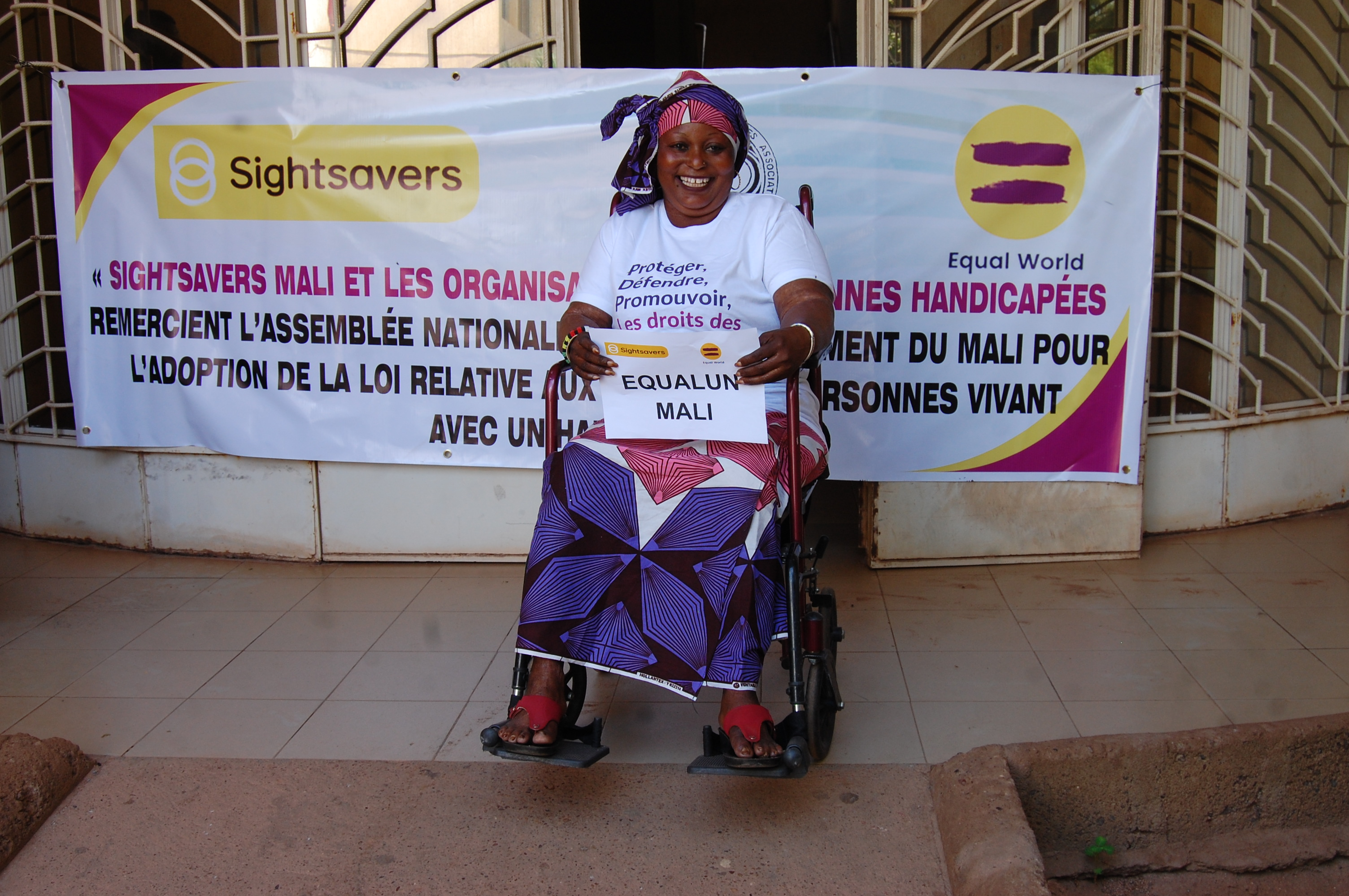 A woman using a wheelchair sitting in front of a disability rights banner for the Equal World campaign.