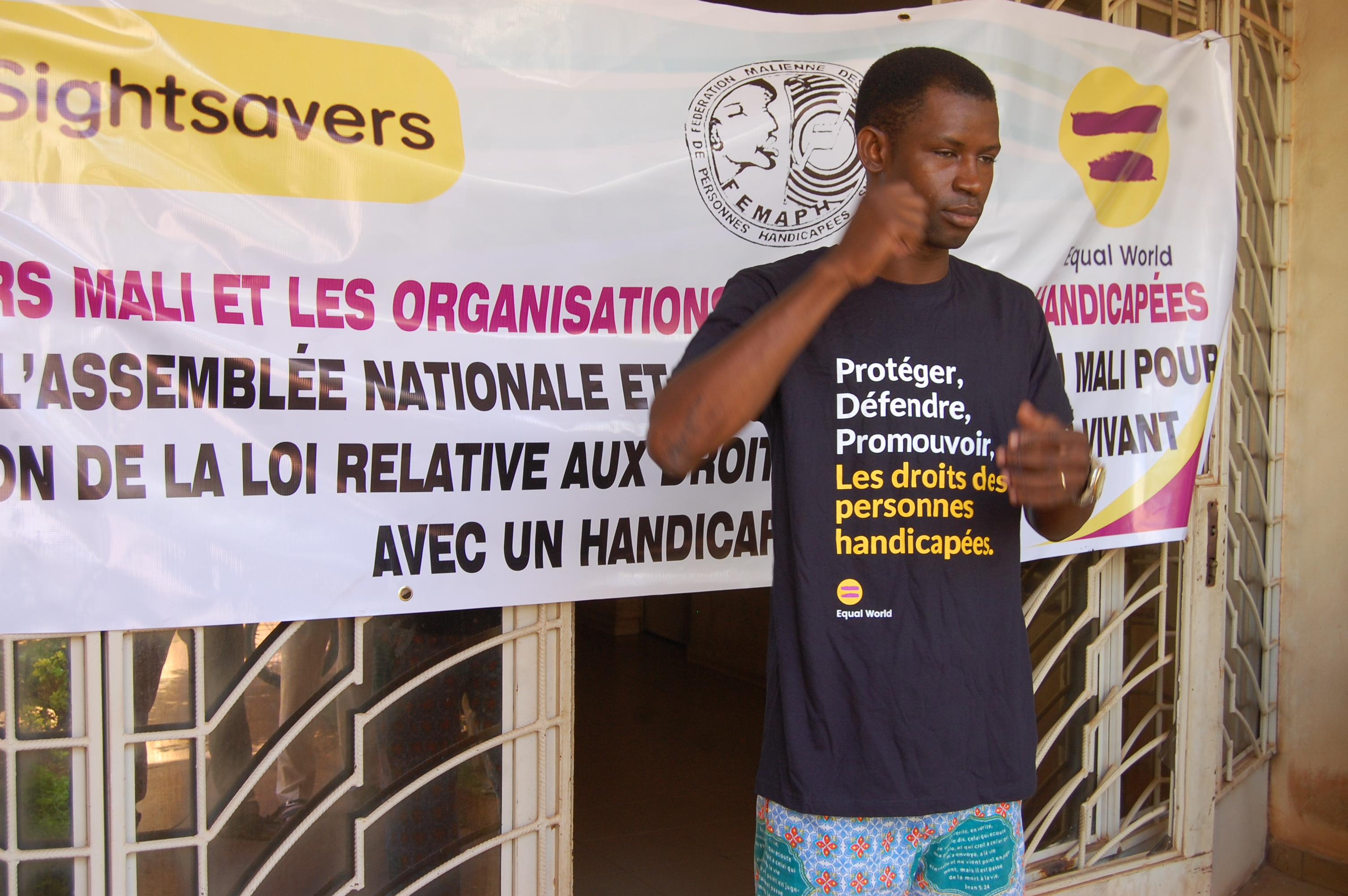 A man using sign language, standing in front of a disability rights banner for the Equal World campaign.