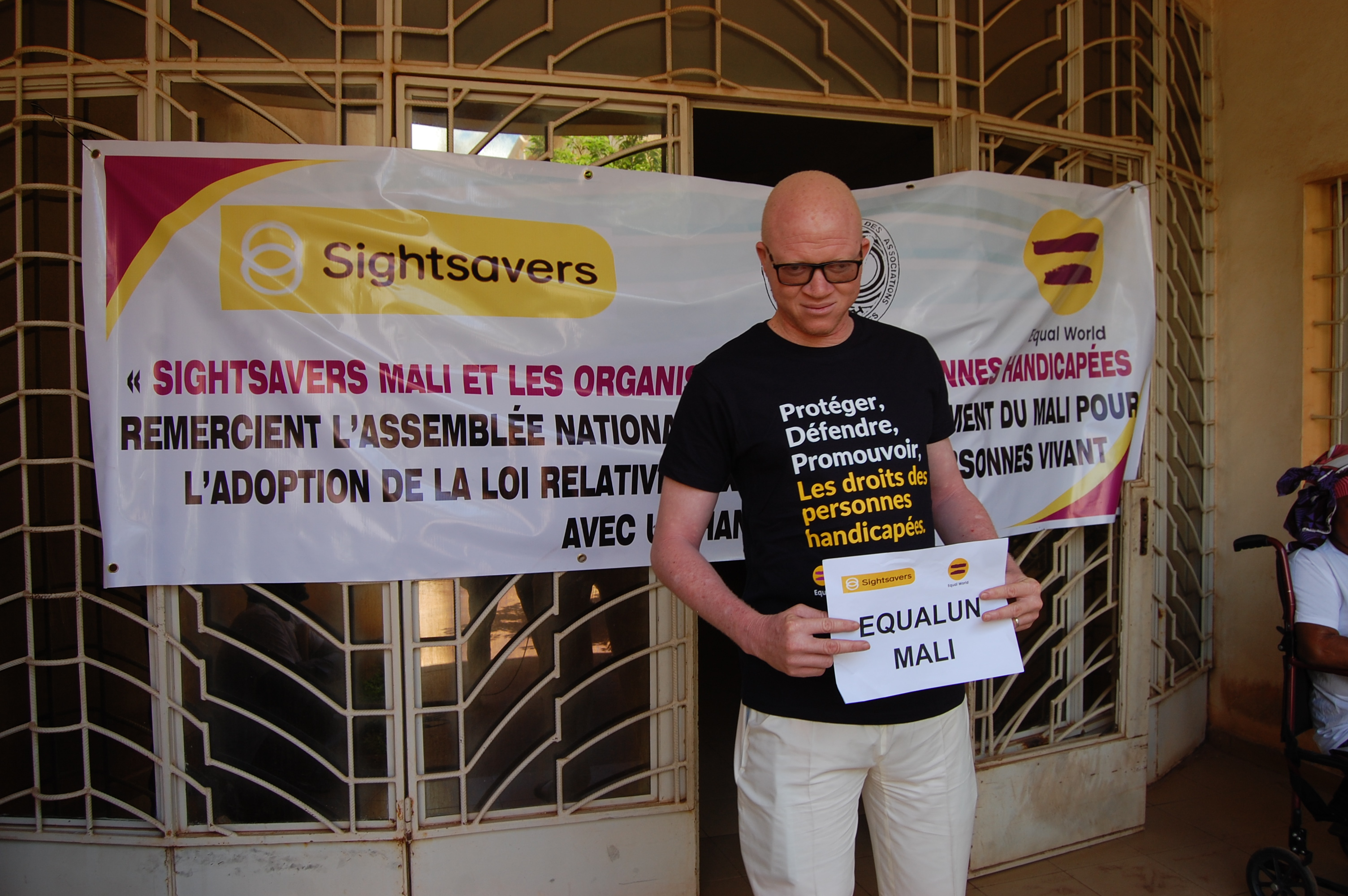 A man with albinism standing in front of a disability rights banner for the Equal World campaign.