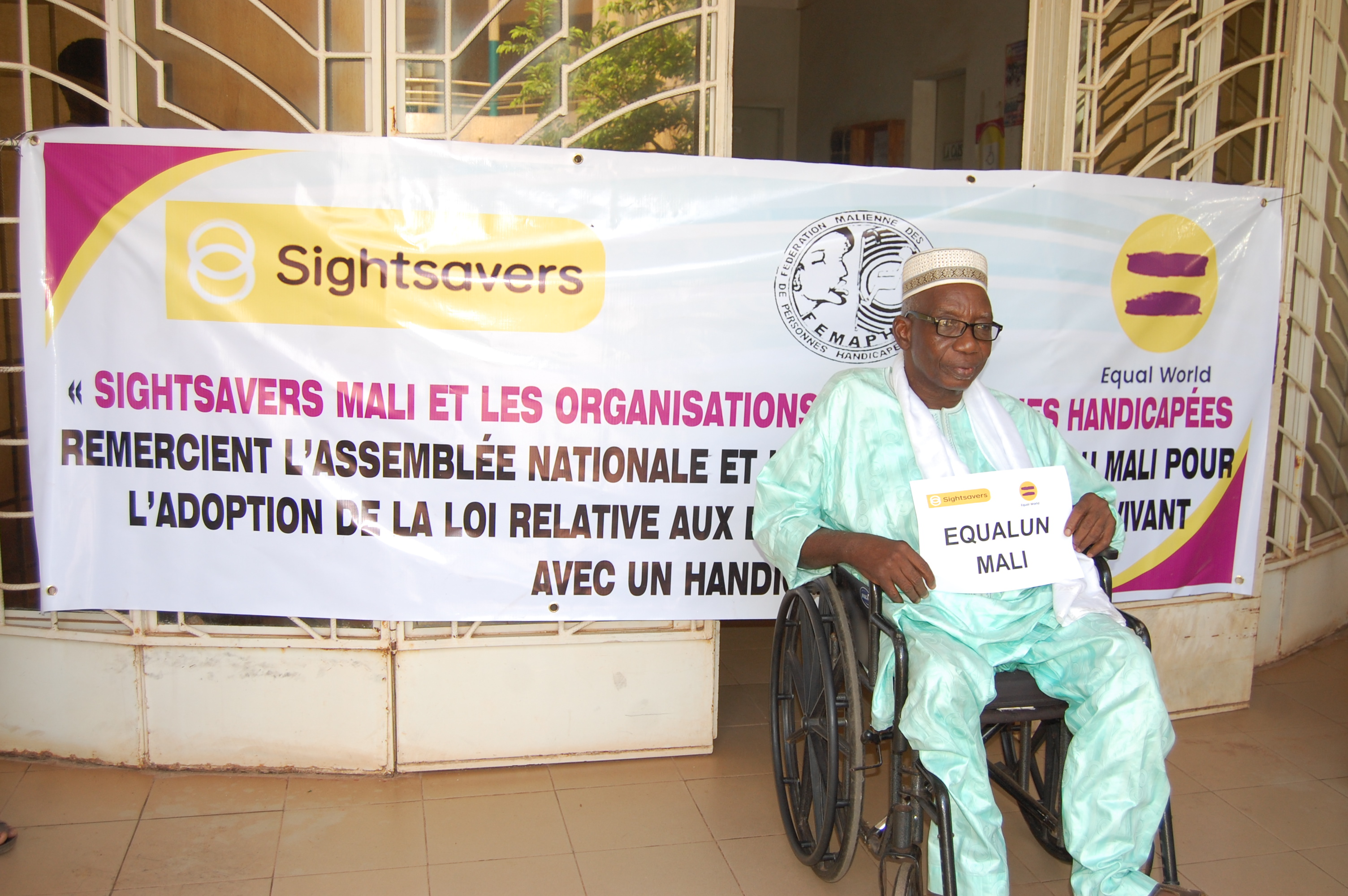 A man using a wheelchair sitting in front of a disability rights banner for the Equal World campaign.