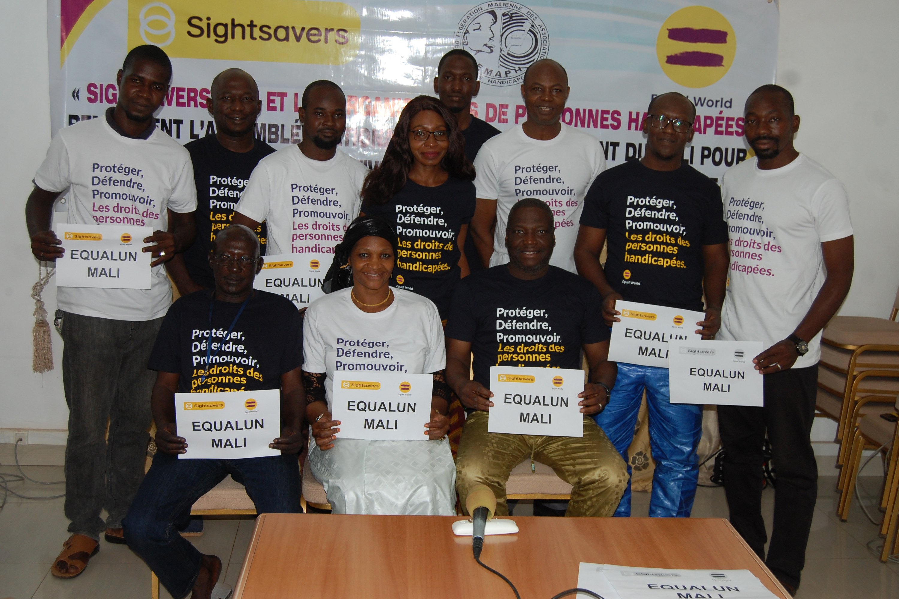 A group of eleven adults posing together, all wearing t-shirts that say 'Protect. Defend. Promote. Disability rights'.