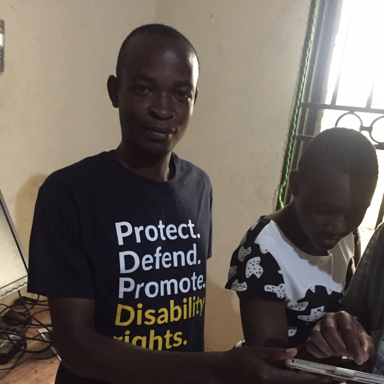 A young man assists a young woman to sign a petition with her finger on a tablet screen.