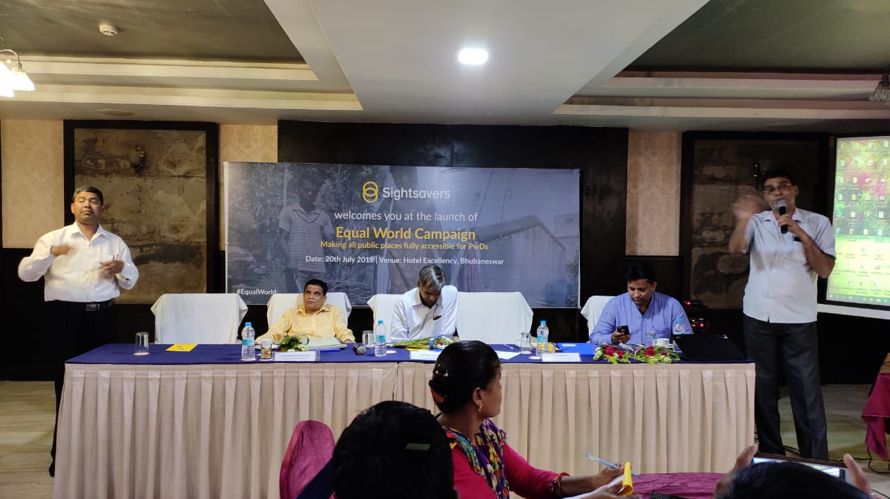 A conference room with three people seated at a long table. One person is standing and speaking, another is doing sign language translation. The event banner reads 'Sightsavers welcomes you at the launch of Equal World Campaign - Making all public places fully accessible for people with disabilities. Date: 20th July 2019. Venue: Hotel Excellency, Bhubaneswar.