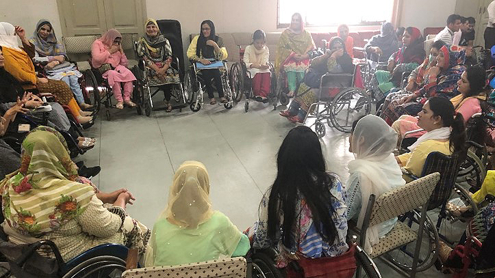 A large group of women sitting in a circle. Many of them are wheelchair users.
