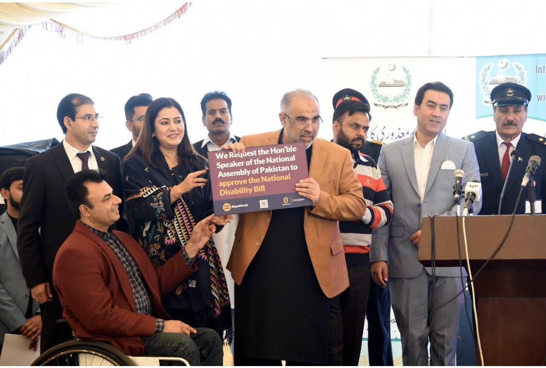 A group of people standing together, holding a sign that shares the petition call for Pakistan.