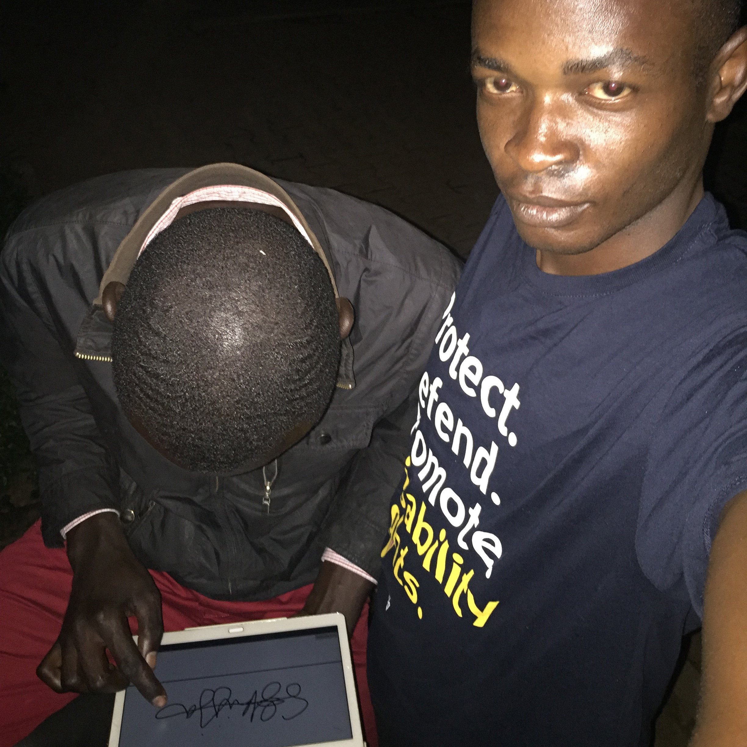 A young man taking a selfie of himself with another man, who is using his finger to sign his name on a tablet screen.