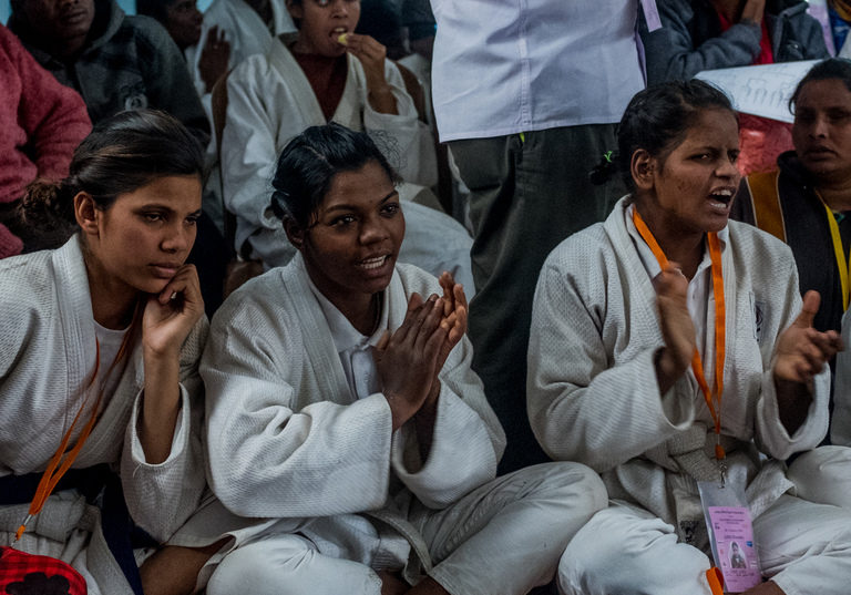 A group of young women in judo uniforms sit on the side of a mat cheering.