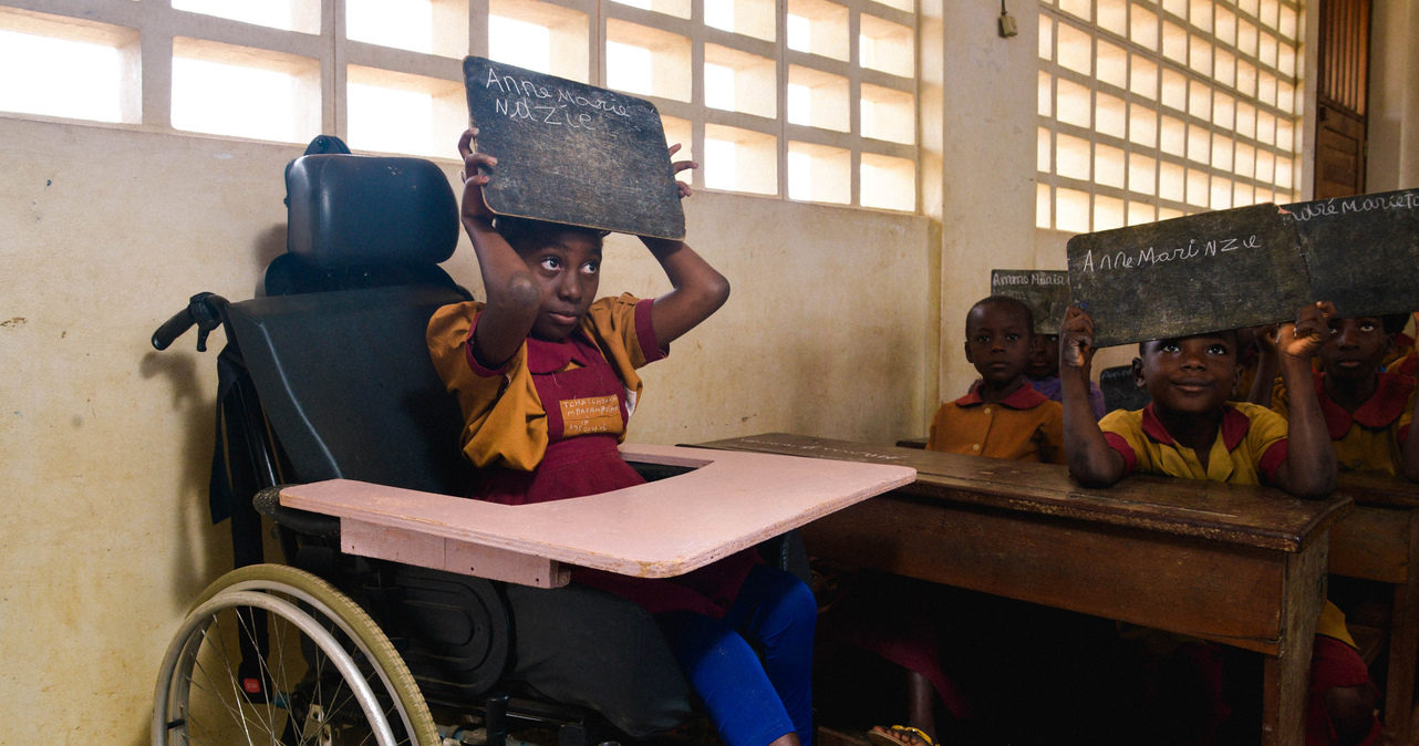 A young girl using a wheelchair holds a blackboard slate above her head in a classroom.