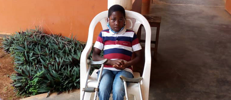 A young boy sits in a chair with crutches either side of him.