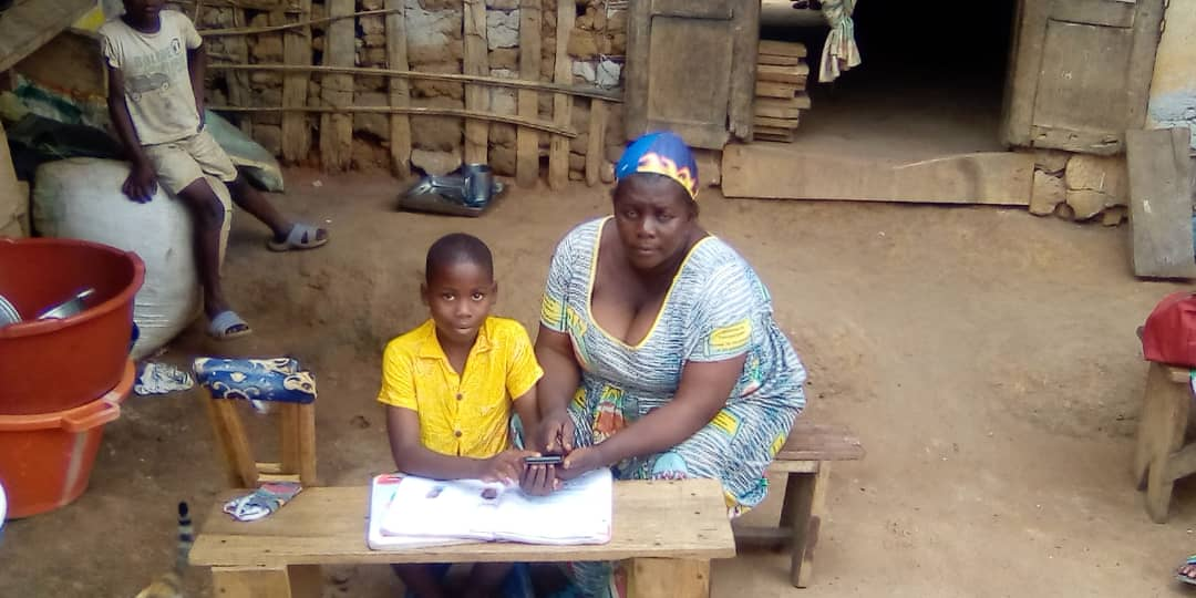A young boy with his mother, working on a table outside.