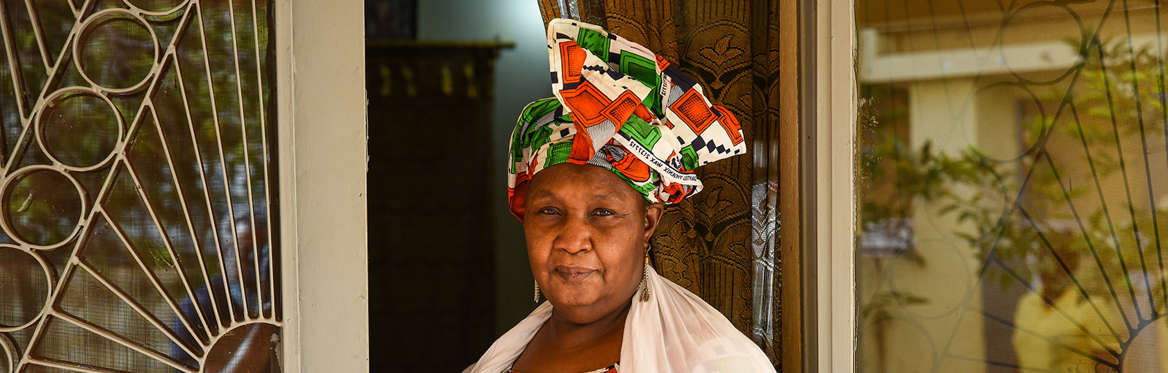 A woman wearing a large colourful head wrap standing in a doorway.