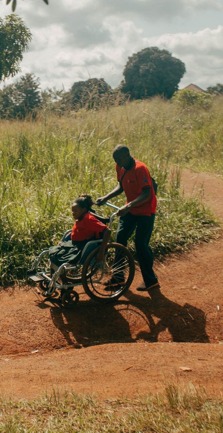 Two silhouetted figures outside. One is a wheelchair user and is being pushed along the road by the other.